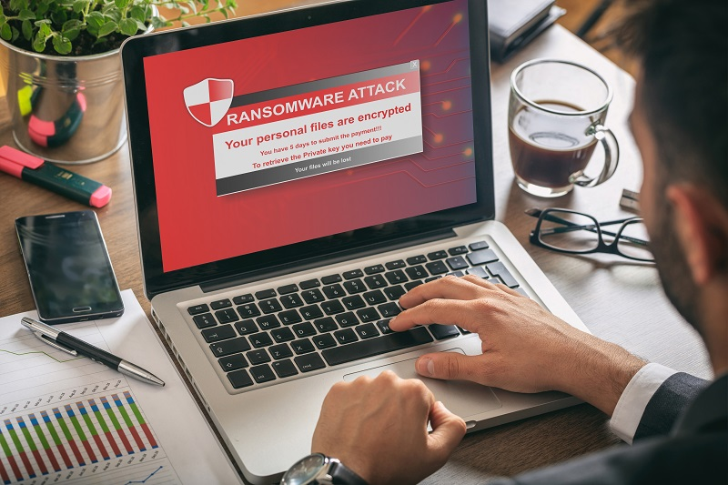 Ransomware alert message on a laptop screen - man at work